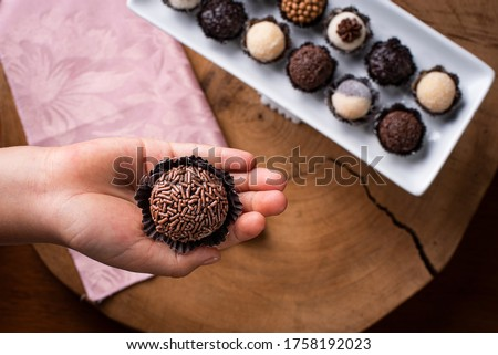 A child's hand holding a brigadeiro. Typical Brazilian sweet. Many types of brigadiers together in the background Royalty-Free Stock Photo #1758192023