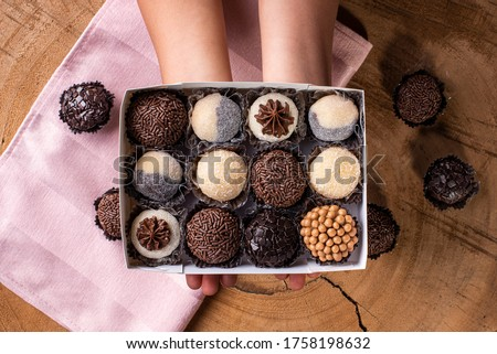 A child's hand holding a Brigadeiro box. Typical Brazilian sweet. Some brigadiers together in the background Royalty-Free Stock Photo #1758198632