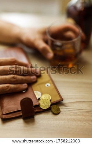 Man drinks alcohol on the last money. Wrinkled alcoholic sits at brown wooden table with a glass of cognac with ice, on the table, empty wallet with coins Royalty-Free Stock Photo #1758212003
