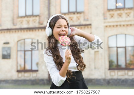 i am a star. girl in headphones. little girl in classy uniform eat lollipop. back to school. modern education with new technology. kid at schoolyard. imagine she is singer. child has music break. #1758227507