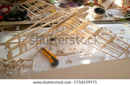Making model airplane from balsa wood. handcrafted on work table Royalty-Free Stock Photo #1758239975