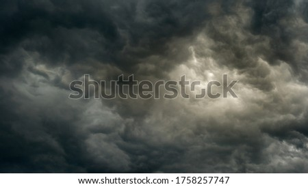 gray moody dramatic sky before the storm with unusual bizarre patterns of thick cumulus clouds and back light. panoramic view. Artistic picture for mystical design or decoration