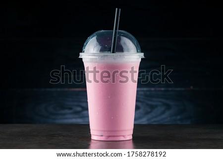 Diet Food and healthy nutrition. Pink Fruit smoothie, cherry milkshake in plastic glass on a dark background. cherry milkshake in takeaway cup #1758278192