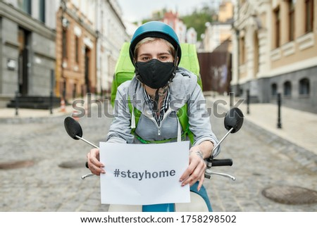Young delivery woman in mask with thermo backpack holding a card with the inscription Stay Home, delivering food on a motor scooter. Focus on face. Courier, delivery service, lockdown concept