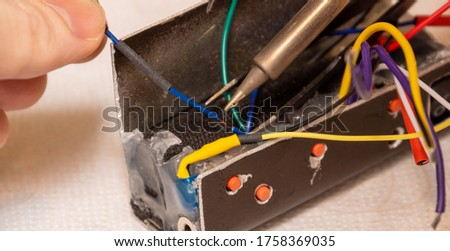 A drop of solder on a soldering iron tip. Soldering wires using a soldering station. DIY bluetooth receiver. #1758369035