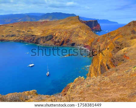 Dry landscape and bay with yachts. Calm blue ocean with anchoring ships. Travel picture from hiking trip. View from shore.