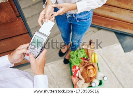 Horizontal from above shot of unrecognizable young woman paying for fresh food delivery service with her debit card