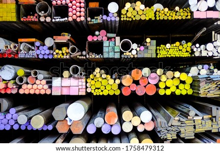 The storage shelf girder perspective view of colorful metal stuff such as cast iron round bar, steel angle, metal pipe. They are raw materials of metalwork, construction for contractors or factory. #1758479312