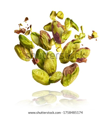 Flying in air fresh raw whole and cracked pistachios  isolated on white background. Concept of Pistachios is torn to pieces close-up. High resolution image #1758485174