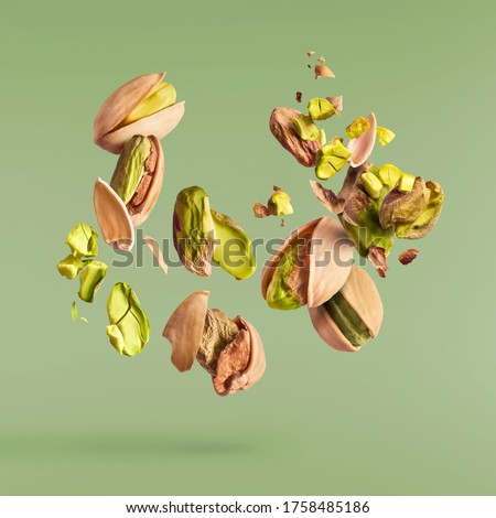 Flying in air fresh raw whole and cracked pistachios  isolated on green background. Concept of Pistachios is torn to pieces close-up. High resolution image #1758485186
