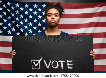 Presidential elections 2020 in USA. Black woman holding Vote sign against american flag #1758492200