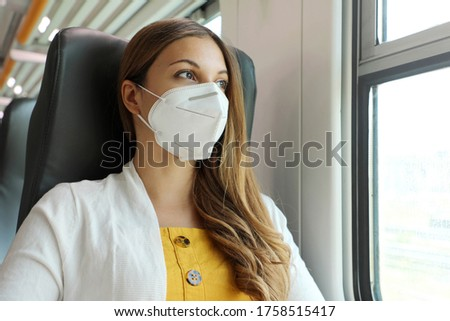 Travel safely on public transport. Young woman with KN95 FFP2 face mask looking through train window. Train passenger with protective mask travels sitting in business class looking through the window. #1758515417