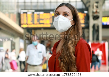 Traveler woman wearing KN95 FFP2 face mask at the airport. Young caucasian woman with behind timetables of departures arrivals waiting worried information for her flight. #1758572426