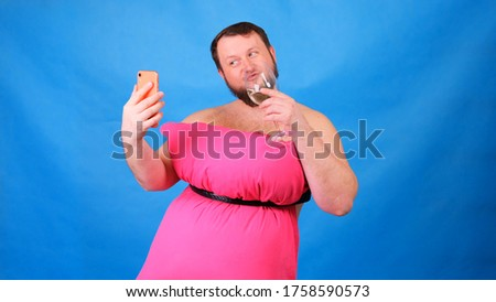 Funny bearded guy in a pink dress made of pillows with a glass of wine makes selfie on a blue background. Crazy quarantine. Funny house cleaning. Fashion 2020. Put on a pillow. Challenge 2020 due to