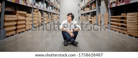 Asian shopper man sitting between cardboard box shelves aisle in warehouse choosing what to buy. Shopping lifestyle in department store. Buying or purchasing factory goods. Inventory industry concept Royalty-Free Stock Photo #1758628487