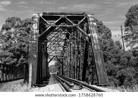 Black and white picture. The old railway bridge is made of steel for over 70 years. Rusted and dirty. Located in Southeast Asia