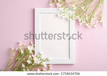 White empty photo frame mockup with mouse-ear chickweed flowers on pink background, top view copy space