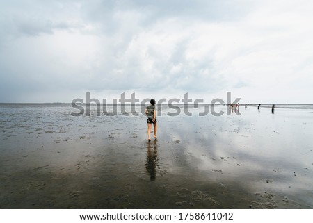 Young woman walking in a calm and tranquil beach at low tide in Wadden Sea, Germany Royalty-Free Stock Photo #1758641042