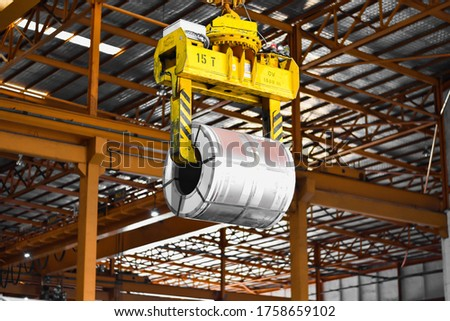 Overhead crane lift up steel coil with tong in wearhouse. Steel coils handling equipment. Steel warehouse and logistics operations. #1758659102