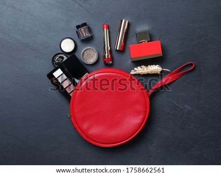 Cosmetic bag with makeup products on black slate background, flat lay