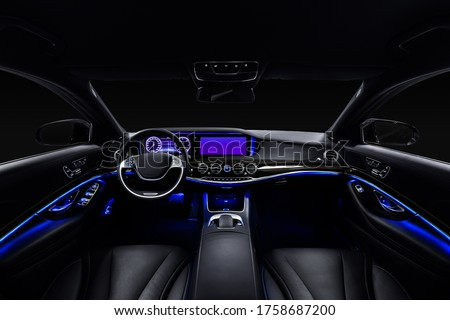 Car interior from driver seat view. Black leather cockpit with blue ambient light. #1758687200