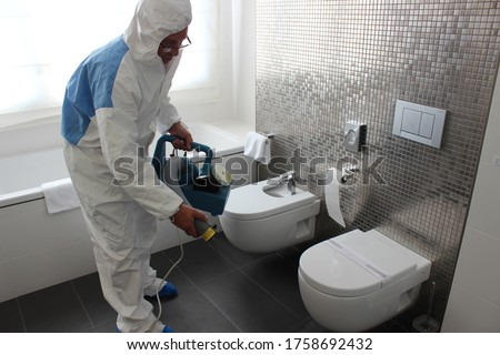 a technician is sanitizing an hotel room in Prague, using steam and ozone,  after the coronavirus SARS-CoV-2 COVID-19 pandemic Royalty-Free Stock Photo #1758692432