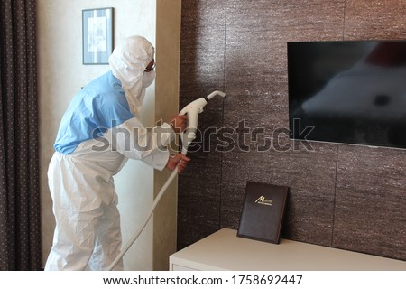 a technician is sanitizing an hotel room in Prague, using steam and ozone,  after the coronavirus SARS-CoV-2 COVID-19 pandemic Royalty-Free Stock Photo #1758692447