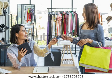 Young woman clothing shop owner holding tablet device receiving credit card payment from a female customer holding shopping bags inside a fashion clothing store. #1758705728