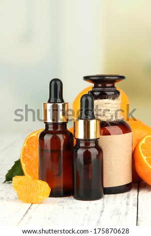 Tangerine essential oil and tangerines on wooden table #175870628