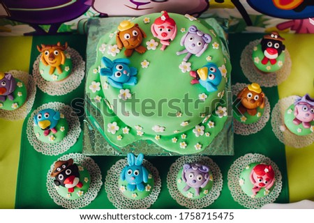 festive children's table with a beautiful cake decorated with green and multi-colored biscuits. candy. Children's birthday.Cake for children's birthday in cartoon style