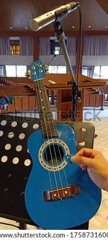 This is a Ukulele with a hand holding a pic.