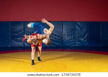 The concept of fair wrestling. Two greco-roman  wrestlers in red and blue uniform wrestling   on a yellow wrestling carpet in the gym #1758734378