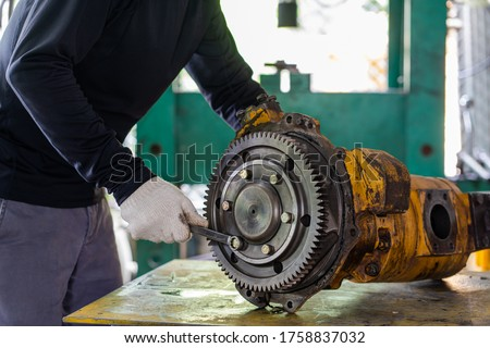 Professional mechanic man inspection hydraulic gear pump of wheel loader in workshop, repair maintenance heavy machinery  Royalty-Free Stock Photo #1758837032