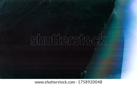 Damaged screen overlay. Broken glass texture. Dark distressed LCD with blue iridescent noise dust. Royalty-Free Stock Photo #1758920048