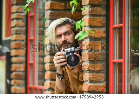 he is spy. professional photographer use vintage camera. bearded man hipster take photo. photo shooting outdoor. brutal man traveler with retro camera. photography in modern life. travel tips.