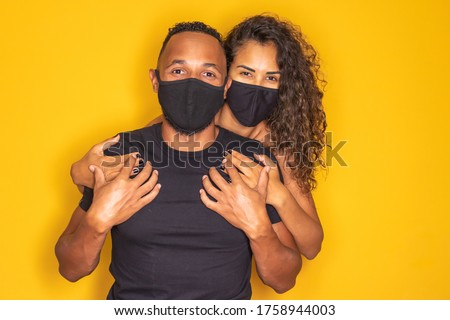Afro valentine couple with mask on yellow background. Covid-19 #1758944003