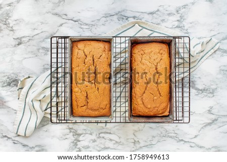 Two freshly baked loaves of pumpkin bread resting on a cooling rack over a white and grey marble background. Image shot from top view, flatlay.