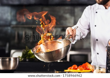 Chef hands keep wok with fire. Closeup chef hands cook food with fire. Chef man burn food at professional kitchen. #1758966962