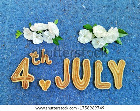 The text of the inscription on July 4 and two mini hearts in the form of pancakes and small lively white ones flower on a blue background with an interesting texture.  America Independence Day