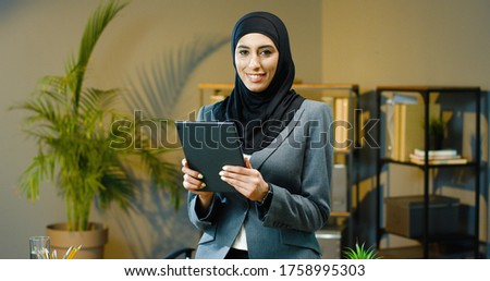 Portrait of beautiful Arab business woman using tablet in modern office. Royalty-Free Stock Photo #1758995303