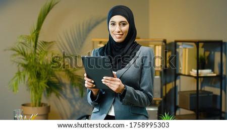 Portrait of beautiful Arab business woman using tablet in modern office. #1758995303