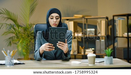 Beautiful Arab business woman using tablet for video conversation in modern office. Royalty-Free Stock Photo #1758995324