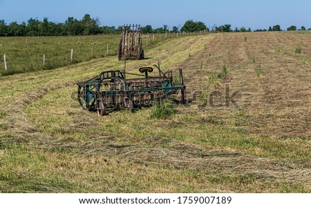 Horse drawn farm equipment in a Amish farms field.  Pictured is a hay rake and a hay elevator