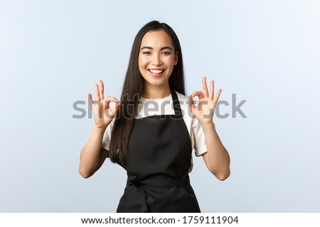 Coffee shop, small business and startup concept. Smiling attractive korean female barista, waitress in cafe, black apron assure clients, show okay sign and grinning, no problem, guarantee quality