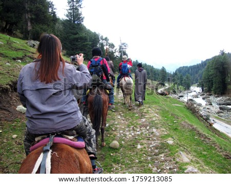 blurred picture of Tourists riding horses to watch the nature.on the moutains of Laripora village Pahalgam, Jammu and Kashmir, India
