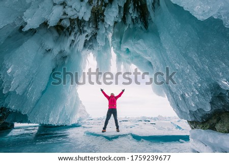 Male tourist in red clothes on Lake Baikal, Russia. Stunning ice cave, red background picture.