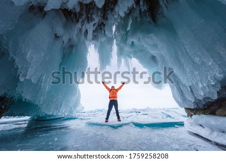 Male tourist in orange clothes on Lake Baikal, Russia. Stunning ice cave, blue background picture.