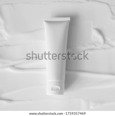 Mockup white plastic tube for moisturizer, lotion, facial cleanser or shampoo on smudged cream texture background top view. Delicate purity skin care product Royalty-Free Stock Photo #1759357469