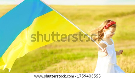 Ukraine s blue-yellow flag flying in wind in hands of little Ukrainian girl on Day of independence of Ukraine. Symbols of Ukraine in hands of a smiling child. Constitution day Ukraine. Soft focus #1759403555