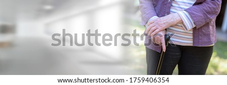 Old woman standing and holding a cane, outdoors; panoramic banner